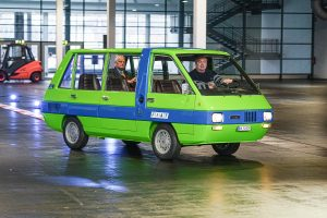 Ein grüner Oldtimer-Bus von Fiat. Zwei Männer sitzen darin.